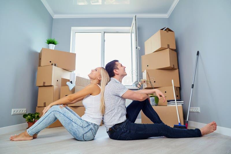 Giovani coppie sul pavimento in una nuova casa immagini stock