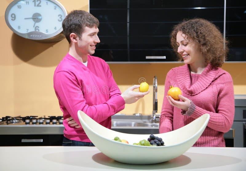 Giovani coppie sulla cucina con la frutta fotografia stock libera da diritti