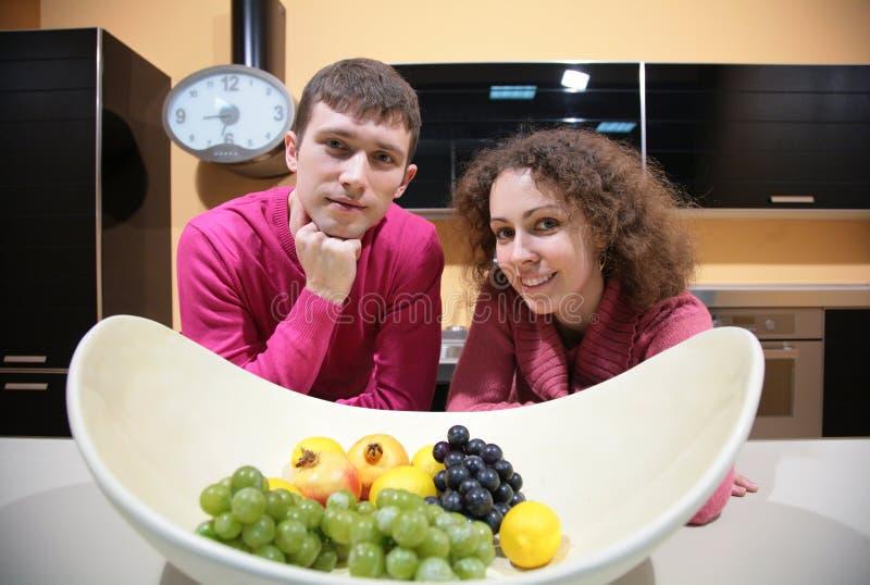 Giovani coppie sulla cucina e vaso con la frutta fotografia stock libera da diritti