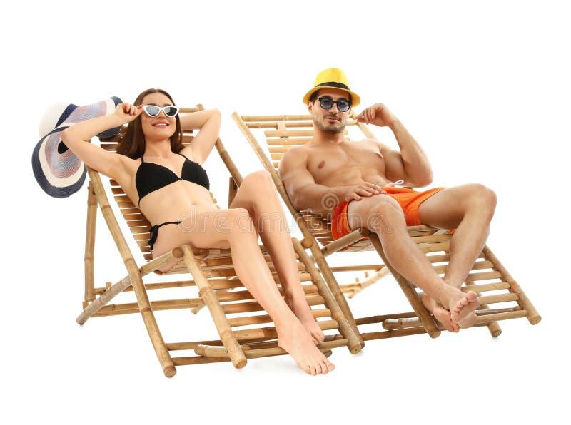Giovani coppie sulle chaise-lounge del sole contro fondo bianco fotografia stock libera da diritti