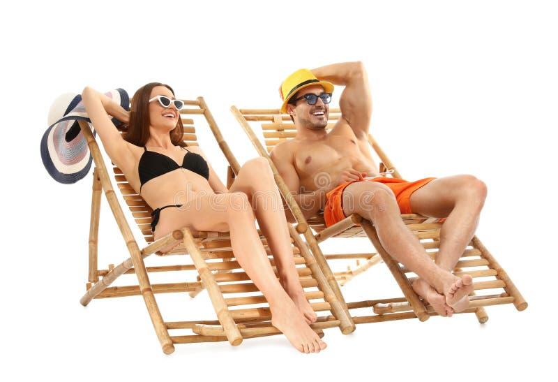 Giovani coppie sulle chaise-lounge del sole contro fondo bianco Spiaggia immagine stock libera da diritti
