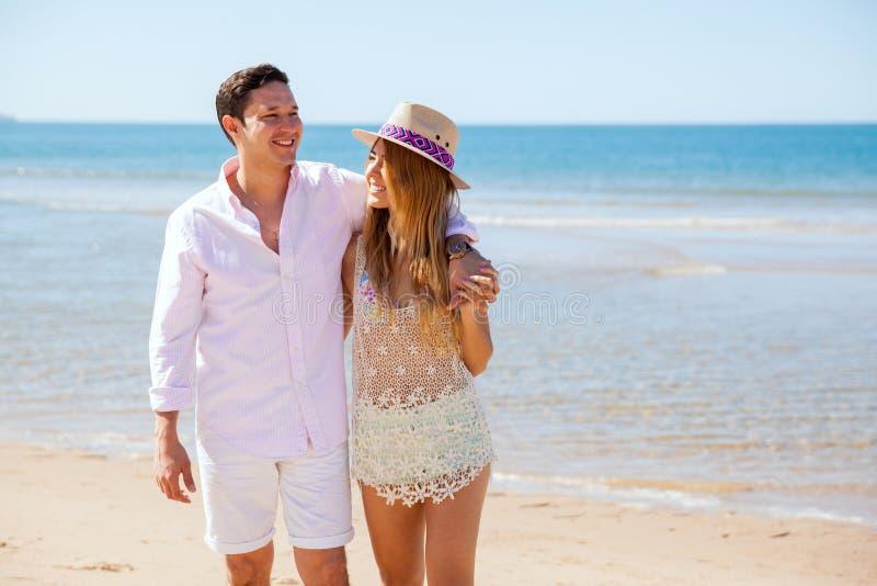 Giovani coppie sveglie che camminano dalla spiaggia fotografia stock libera da diritti