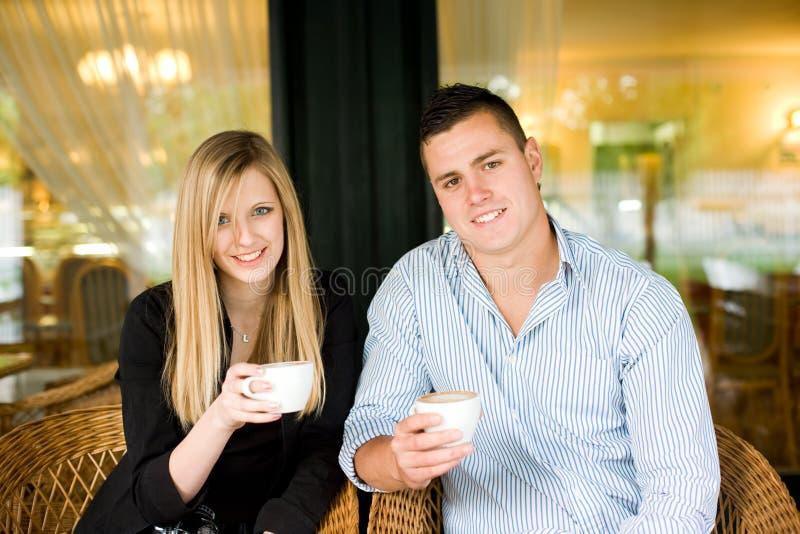 Giovani coppie sveglie che mangiano caffè. fotografia stock