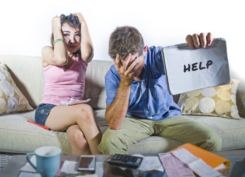 Giovani coppie tristi e preoccupate attraenti che spiegano insieme in strato di sforzo finanziario a casa nel problema domestico  fotografia stock libera da diritti