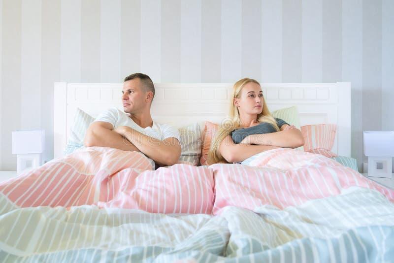 Giovani coppie turbate che hanno problemi coniugali o un disaccordo che si siede parallelamente a letto affronto nelle direzioni  fotografia stock libera da diritti