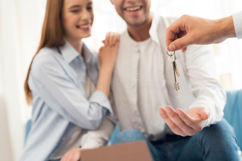 Giovani coppie in una riunione con un agente immobiliare Il tipo e la ragazza stipulano un contratto con la proprietà d'acquisto  fotografie stock libere da diritti