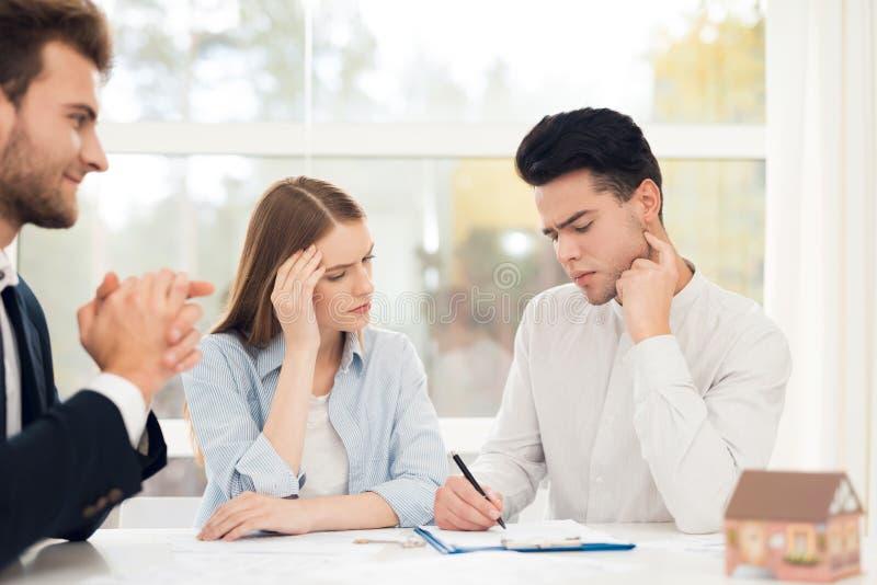 Giovani coppie in una riunione con un agente immobiliare Il tipo e la ragazza stipulano un contratto con la proprietà d'acquisto  immagini stock libere da diritti