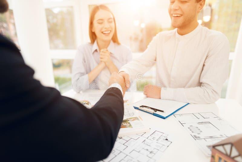 Giovani coppie in una riunione con un agente immobiliare Il tipo e la ragazza stipulano un contratto con la proprietà d'acquisto  immagini stock