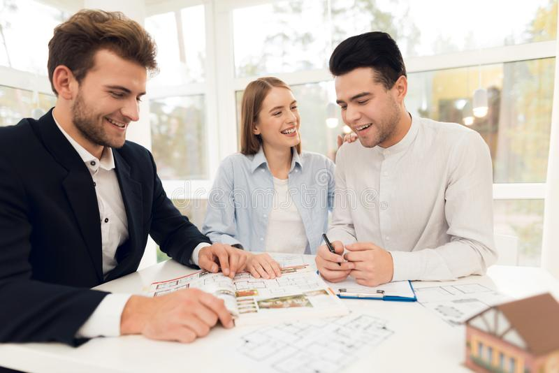 Giovani coppie in una riunione con un agente immobiliare Il tipo e la ragazza stipulano un contratto con la proprietà d'acquisto  fotografia stock libera da diritti