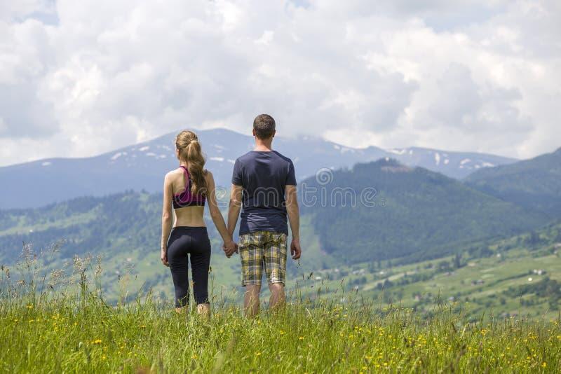 Giovani coppie, uomo allegro e donna esile tenentesi per mano all'aperto sul fondo di bello paesaggio della montagna il giorno di immagini stock libere da diritti