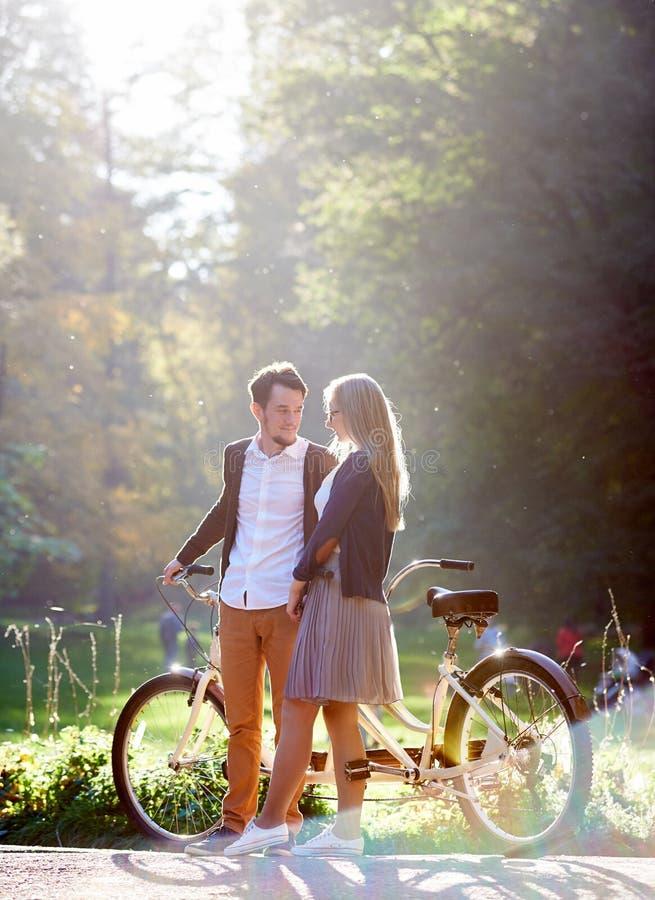 Giovani coppie, uomo bello e donna attraente sulla bici in tandem nel parco o nella foresta soleggiato di estate fotografia stock