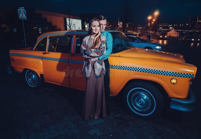 Giovani coppie vicino all'automobile gialla del taxi nella notte Il tipo abbraccia delicatamente la ragazza con gli occhi chiusi  immagini stock libere da diritti