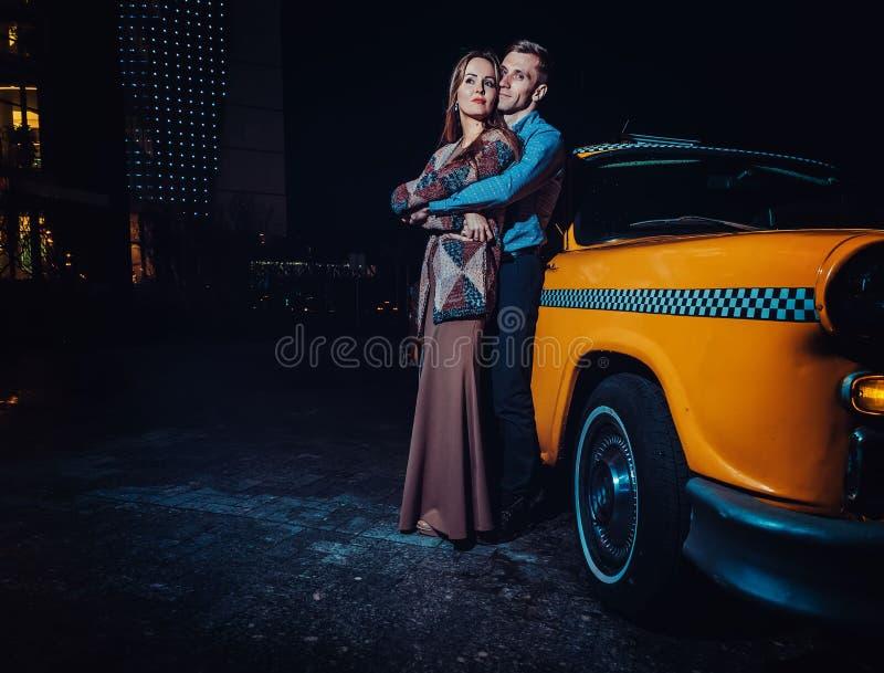 Giovani coppie vicino all'automobile gialla del taxi nella notte Il tipo abbraccia delicatamente la ragazza con gli occhi chiusi  fotografia stock libera da diritti