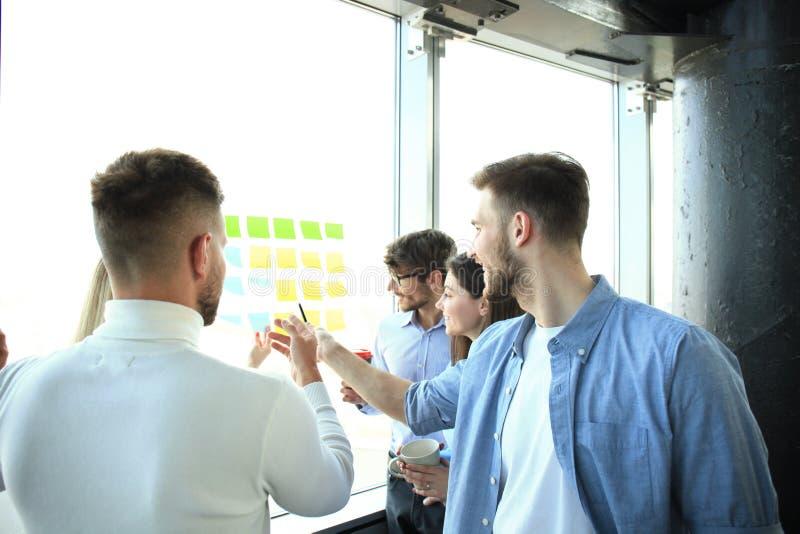 Giovani creativi della giovane impresa sulla riunione all'ufficio moderno che fa i progetti di piani con gli autoadesivi della po fotografie stock
