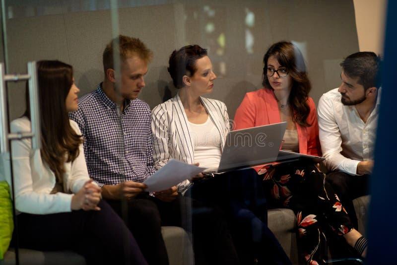 Giovani creativi multirazziali in ufficio moderno Il gruppo di gente di affari sta collaborando con il computer portatile immagine stock