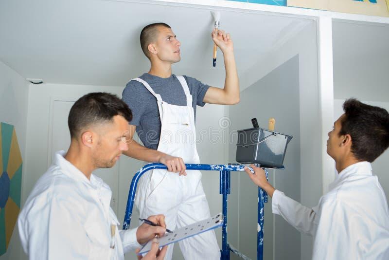 Giovani decoratori che dipingono il supervisore del soffitto scrivono negli appunti fotografia stock