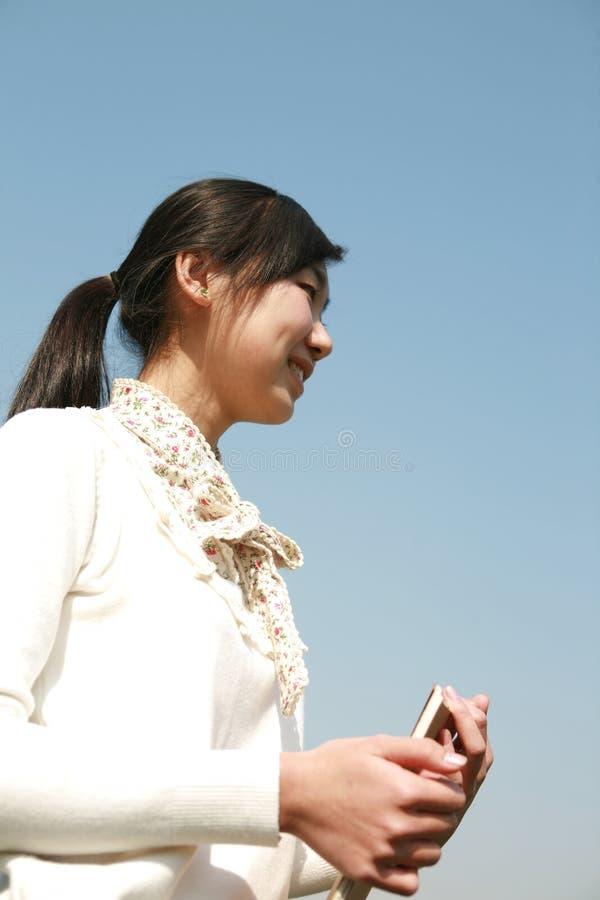 giovani del cielo della holding della ragazza dei libri blu fotografie stock libere da diritti