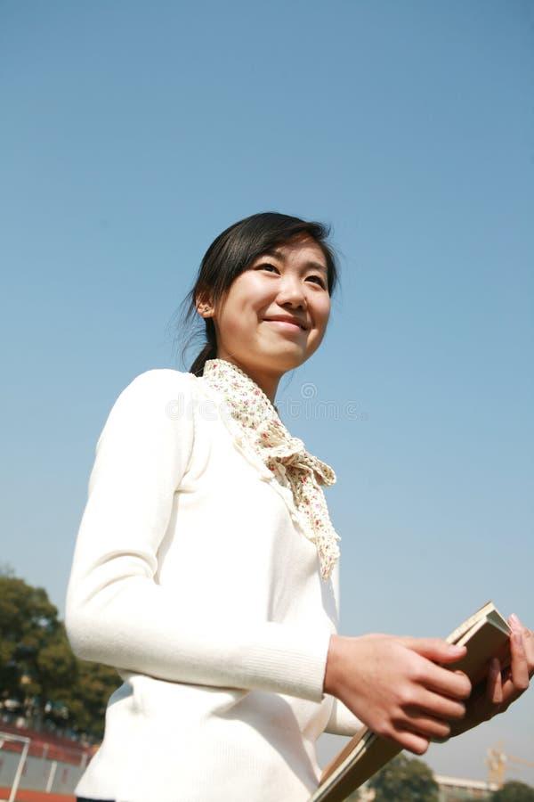 giovani del cielo della holding della ragazza dei libri blu fotografia stock libera da diritti