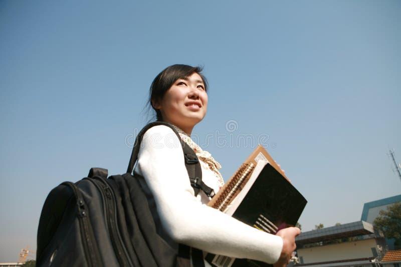 giovani del cielo della holding della ragazza dei libri blu immagini stock