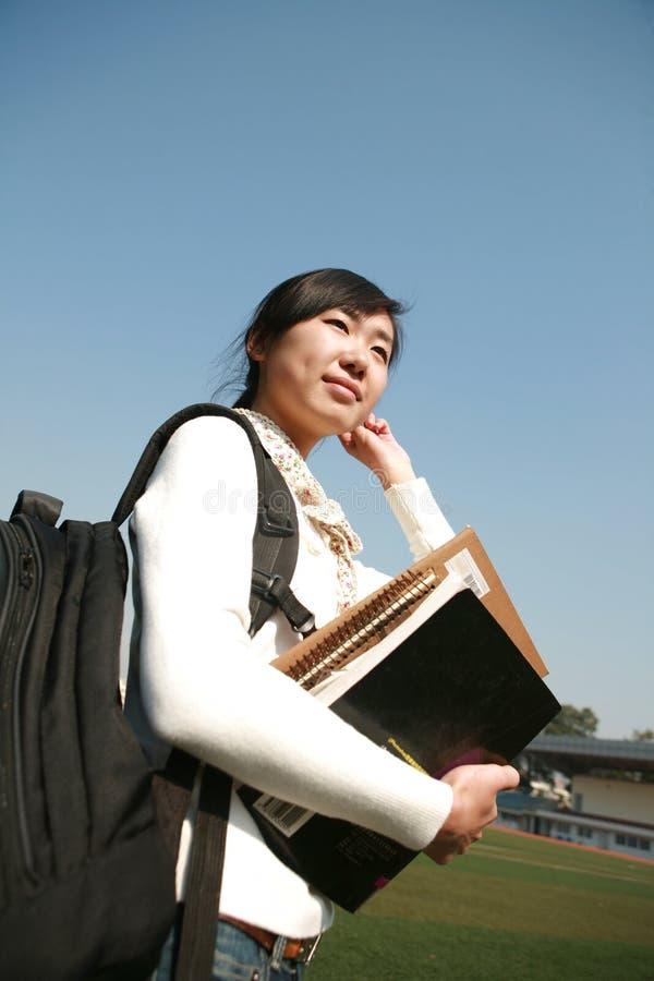giovani del cielo della holding della ragazza dei libri blu fotografia stock