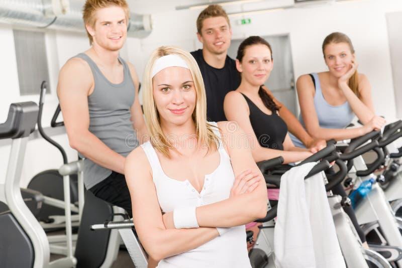 Giovani del gruppo di forma fisica alla bicicletta di ginnastica immagini stock libere da diritti
