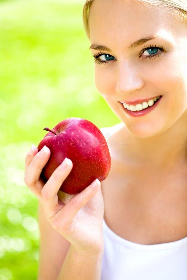 giovani della donna della holding della mela fotografia stock