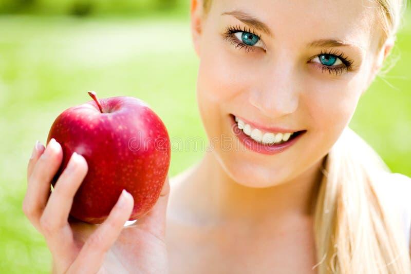 giovani della donna della holding della mela fotografia stock libera da diritti