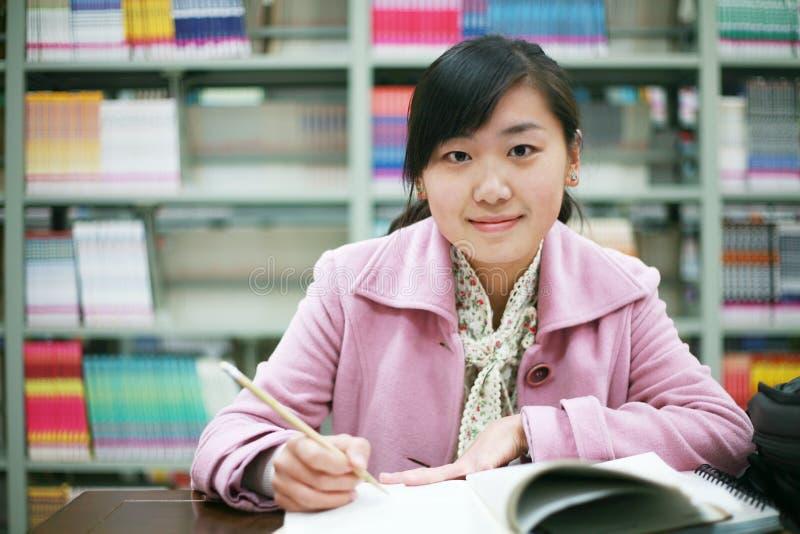 giovani della donna della lettura delle biblioteche fotografia stock