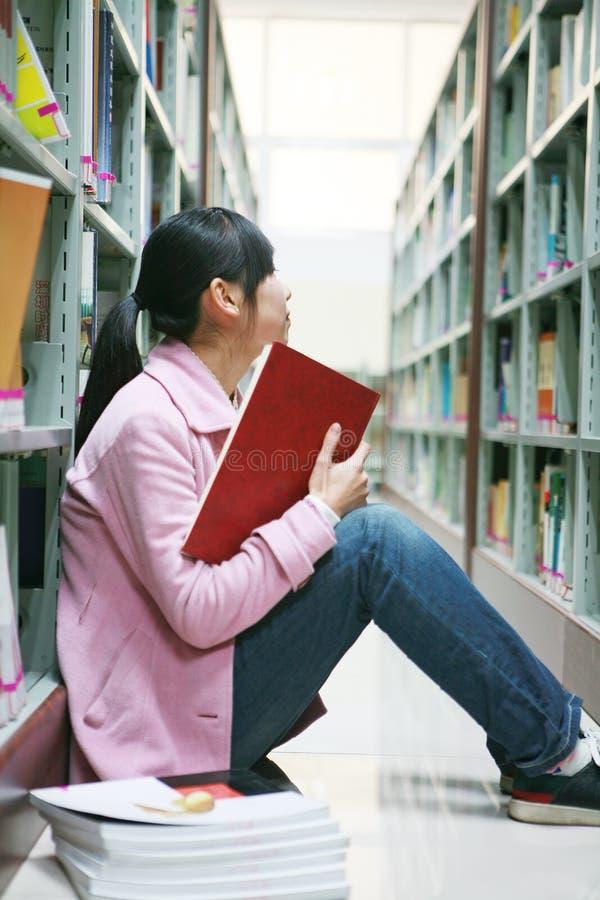 giovani della donna della lettura delle biblioteche immagini stock libere da diritti