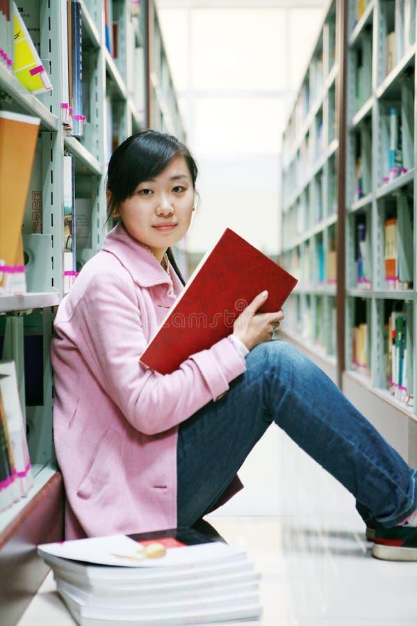 giovani della donna della lettura delle biblioteche immagine stock libera da diritti
