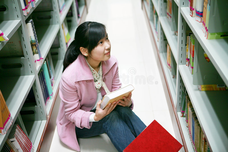 giovani della donna della lettura delle biblioteche fotografie stock