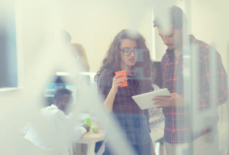 Giovani della giovane impresa, coppie che lavorano al computer della compressa fotografie stock libere da diritti