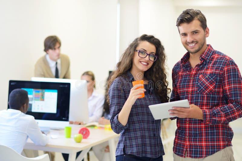 Giovani della giovane impresa, coppie che lavorano al computer della compressa immagine stock libera da diritti
