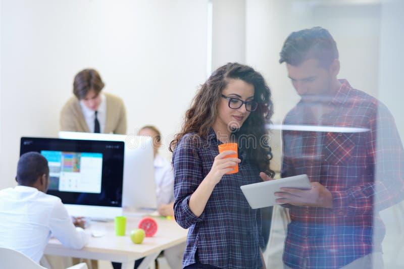 Giovani della giovane impresa, coppie che lavorano al computer della compressa fotografia stock libera da diritti