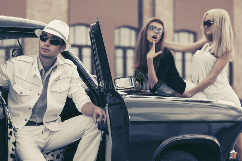 Giovani di modo in macchina d'annata in via della città fotografie stock libere da diritti