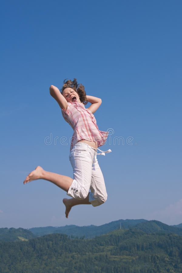 giovani di salto del cielo della ragazza fotografia stock libera da diritti