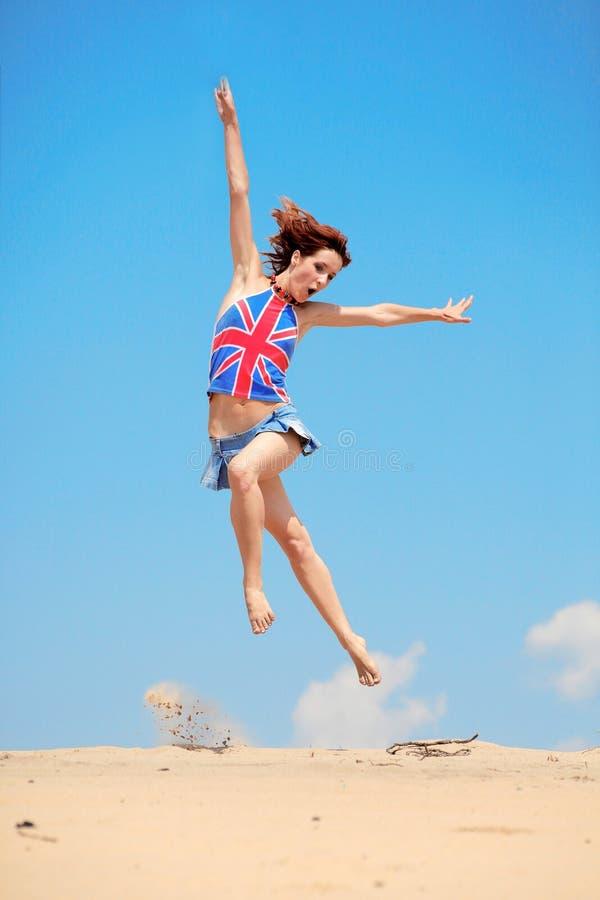 giovani di salto del cielo della ragazza blu della priorità bassa immagine stock