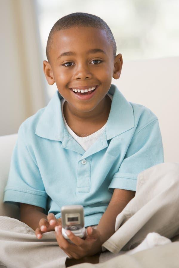 giovani di seduta del testo del sofà di messaggio del ragazzo fotografie stock libere da diritti