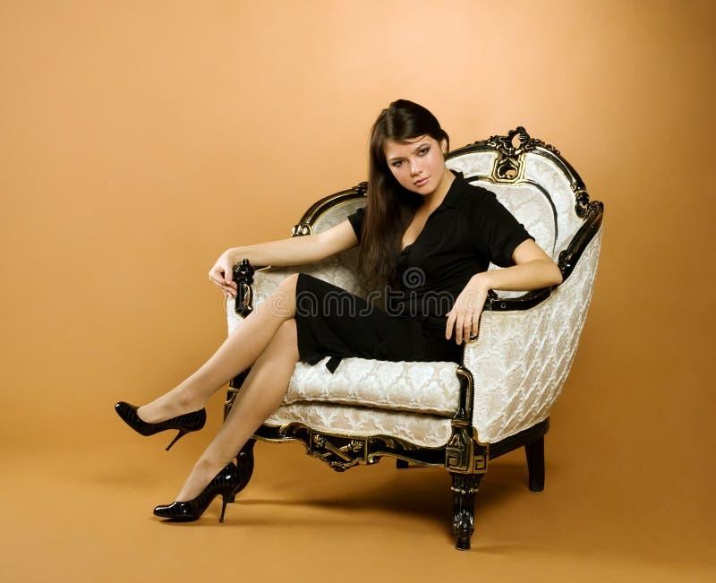 giovani di seduta della donna della poltrona fotografia stock