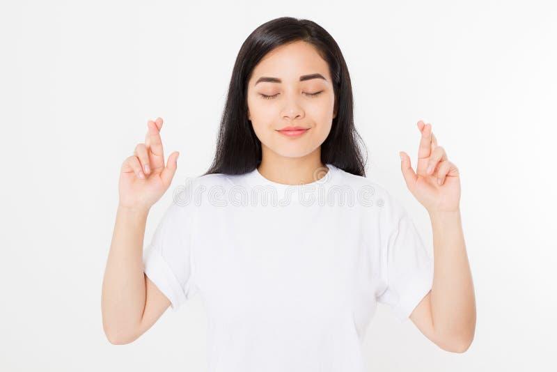 Giovani dita asiatiche dell'incrocio della donna per il desiderio della buona fortuna isolate su fondo bianco Maglietta di estate fotografia stock