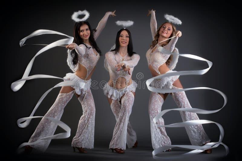Giovani donne adorabili che ballano con i nastri in studio fotografia stock