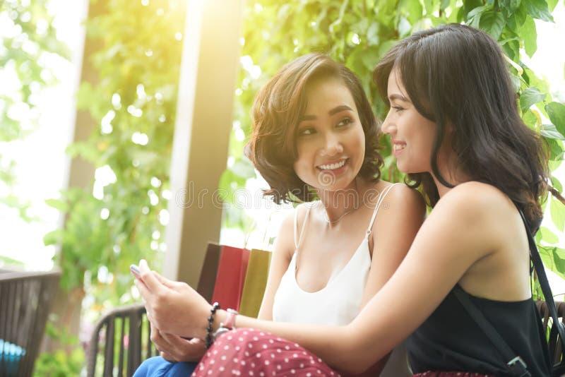 Giovani donne asiatiche con il telefono immagine stock