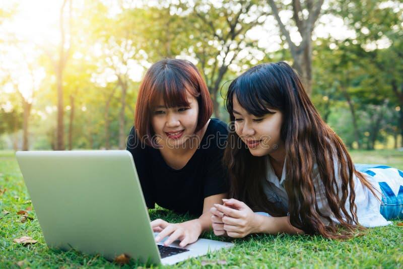 Giovani donne asiatiche dei pantaloni a vita bassa felici che lavorano al computer portatile in parco Studiando nell'erba fotografia stock libera da diritti