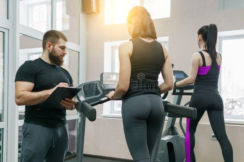 Giovani donne atletiche sulla pedana mobile, sulla donna di preparazione e d'aiuto dell'istruttore personale del cliente Forma fi fotografie stock