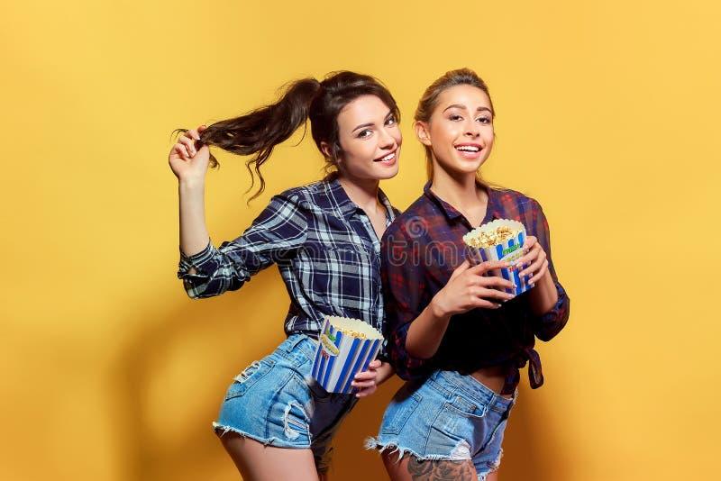 Giovani donne attraenti con popcorn fotografie stock libere da diritti