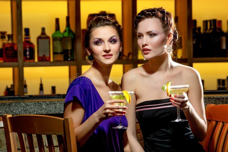 Giovani donne che bevono alla barra fotografie stock