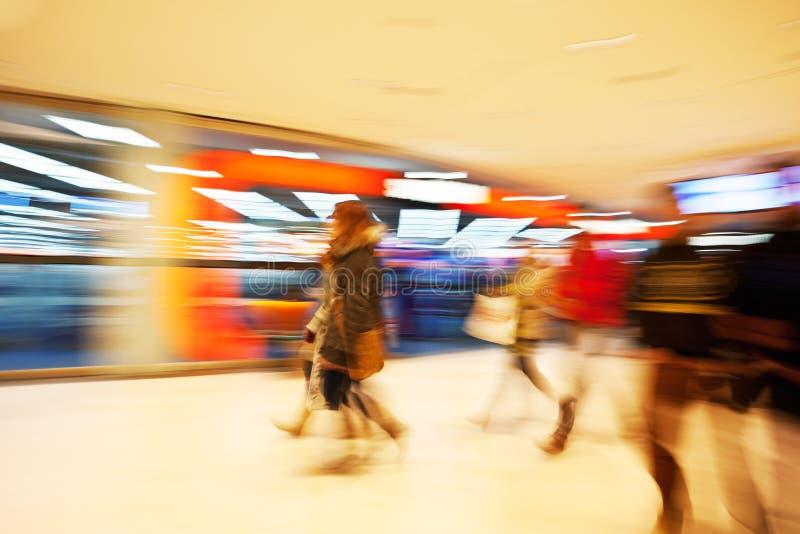 Giovani donne che camminano dopo l'esposizione della finestra nel negozio di vestiti immagini stock