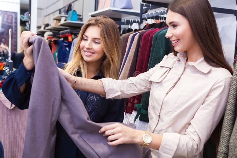 Giovani donne che comperano e che esaminano un certo abbigliamento in un deposito fotografia stock