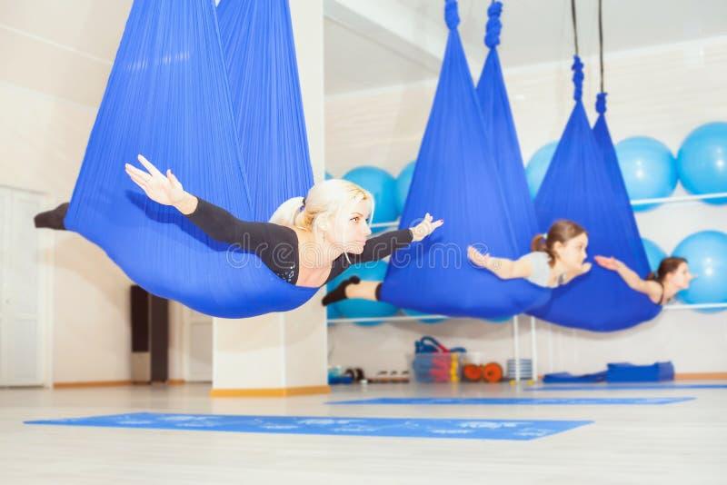 Giovani donne che fanno esercizio aereo di yoga o yoga antigravità immagini stock libere da diritti