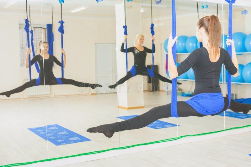 Giovani donne che fanno esercizio aereo di yoga o yoga antigravità fotografie stock libere da diritti
